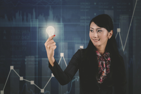 Picture of young businesswoman holding a bright bulb and standing with growth finance graph background Stock Photo