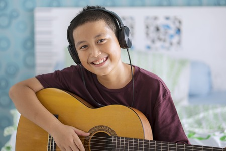 Image of Asian little boy wearing headset while playing acoustic guitar. Shot at home Stock Photo