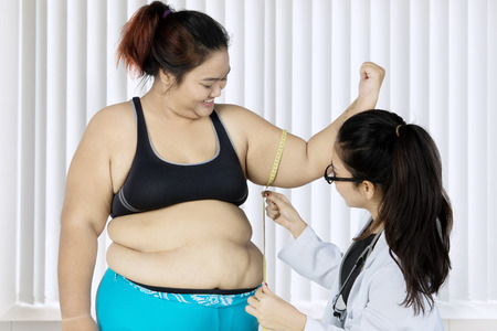 Young female doctor measuring bicep of her fat patient by using a measure tape while examining in the clinic Stock Photo