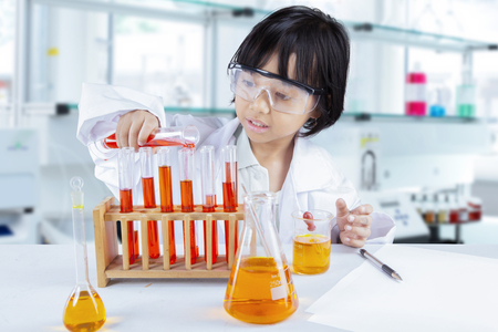 Portrait of clever school girl experimenting chemical liquid while standing in the laboratory