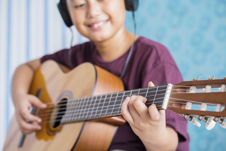 Closeup of little boy playing acoustic guitar while wearing headset. Shot at home Stock Photo