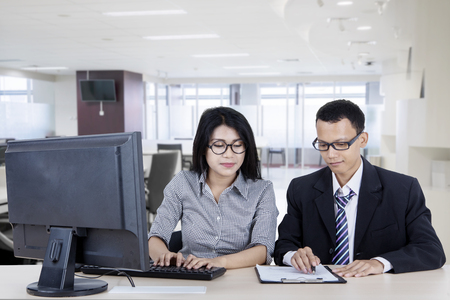 Picture of two business people using a computer while working together in the office
