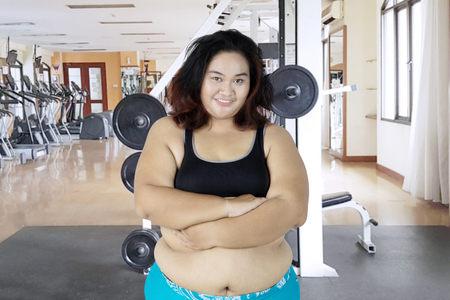 Picture of fat woman crossed her arms while smiling at the camera and standing in the gym center