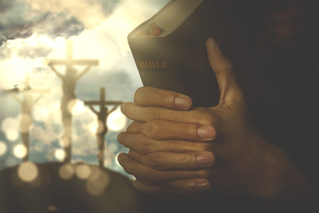 Picture of christian person holding a bible with crucifixion sign on the background