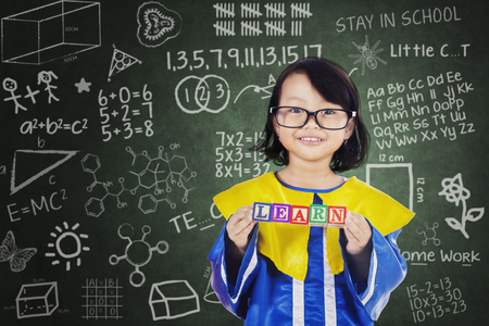 Picture of graduate little girl is showing learn word on the wooden cube while standing with scribbles background. Shot in the classroom