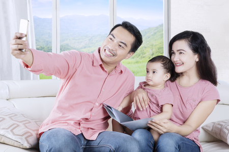 Portrait of smiling family taking selfie photo by using smartphone while sitting on the sofa