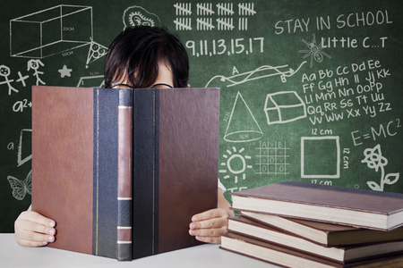 Image of a schoolgirl being covered by a book while reading a book and sitting with scribbles on the chalkboard Stock Photo