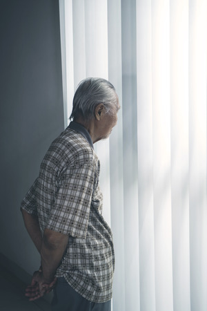 Portrait of a lonely senior man looks pensive in the retirement home while standing by the window
