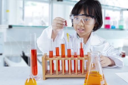 Portrait of an adorable schoolgirl mixing chemical liquids to create experiments in the laboratory