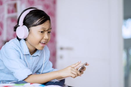 Image of cute little girl enjoying music by using smartphone while singing in the bedroom Stock Photo