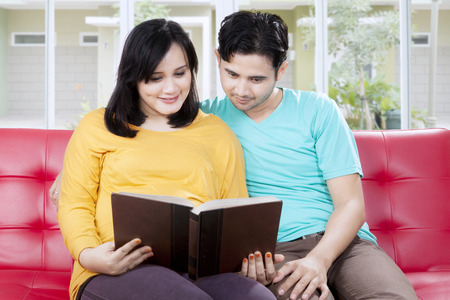 Loving husband reading a book with pregnant wife at home Stock Photo