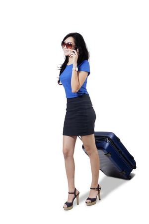 Full length of pretty businesswoman speaking on the mobile phone while pulling a suitcase, isolated on white background Stock Photo