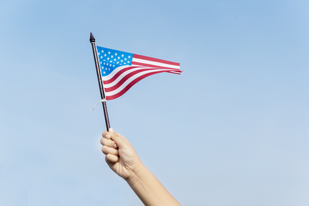 Close up of unknown child hands waving an American flag with blue sky of background Stock Photo