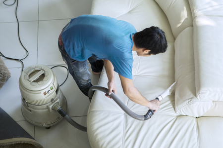 High angle view of male janitor using a vacuum cleaner for cleaning a couch. Shot at home