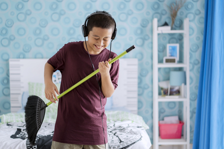Picture of adorable little boy playing guitar with a broom while wearing headset. Shot in the bedroom
