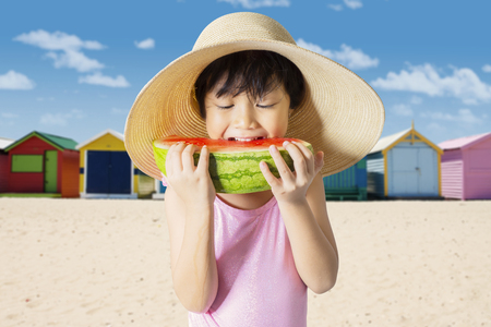 Picture of a little girl eating a slice of watermelon while standing on the beach. Concept of summer
