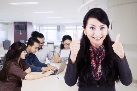 Picture of beautiful leader showing thumbs up with her employees working in the office Stock Photo