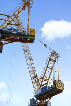 Close up of yellow tower crane on the construction site. Shot with blue sky background