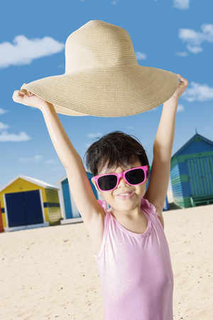 Summer vacation concept. Cute little girl looks happy while lifting her hat and standing on the beach