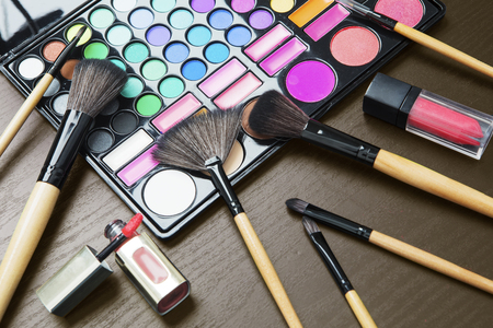 Image of colorful eyeshadow palette with brushes and lipstick for professional makeup tools on the table Stock Photo