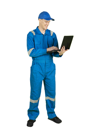 Full length of European male mechanic using a laptop computer while standing in the studio, isolated on white background