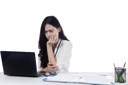 Picture of female entrepreneur looks stressed while working with laptop, isolated on white background