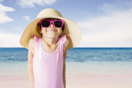 Picture of shy little girl wearing sunglasses and hat while standing on the coast