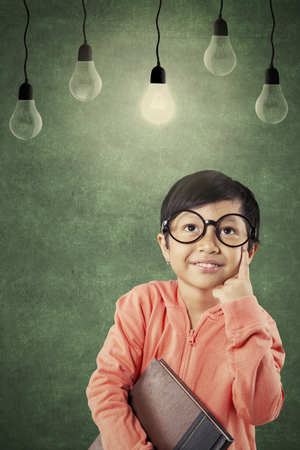 Portrait of cute schoolgirl is holding a book and looking at a bright bulb in the classroom Stock Photo