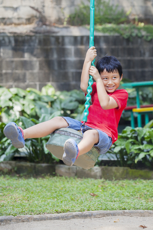 Portrait of adorable little boy looks happy while playing with a flying fox. Shot in the playground