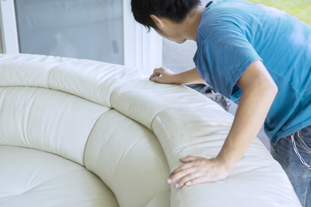 Image of an unknown male worker using a sponge for wiping white leather couch