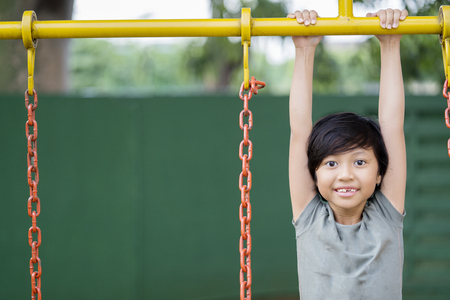 Image of little girl hanging on the bar while playing in the playground Stock Photo