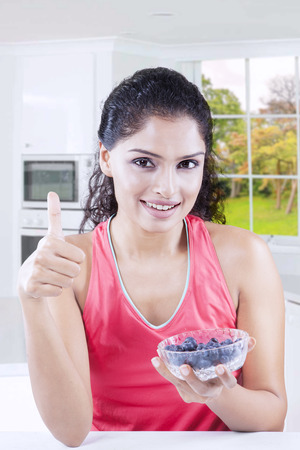Indian woman looking at the camera while holding blueberries in a bowl and showing thumb up with autumn background on the window