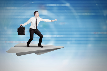 Businessman surfing on a paper plane with futuristic background