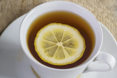 Close up of warm tea with slice of fresh lemon in teacup. Shot above wooden table