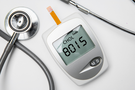 Closeup of medical device for measuring cholesterol with stethoscope on the table, isolated on white background