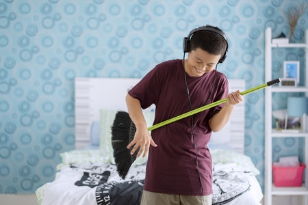 Picture of a cute little boy wearing headset while playing guitar by using broom in the bedroom