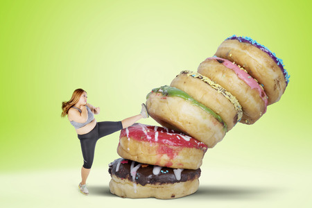 Picture of fat woman refusing to eat sweet food by kicking a pile of donuts. Shot with green screen background