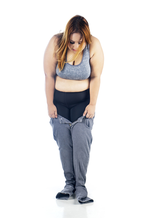Portrait of fat woman looks unhappy while trying to wear tight jeans, isolated on white background