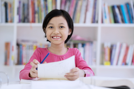Picture of cute schoolgirl smiling at the camera while taking notes on a paper. Shot in the library