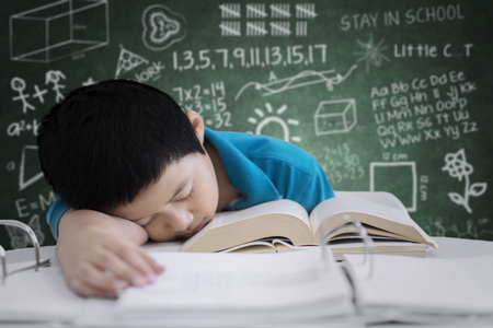 Image of Asian preteen student looks tired after studying in the classroom with scribbles on the chalkboard