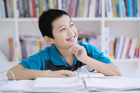 Image of handsome preteen student looks pensive while studying in the library