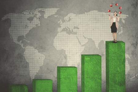 Picture of beautiful female entrepreneur juggling red balls while standing above growth chart with world map background