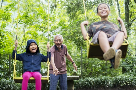 Das Bild von zwei Kindern sieht glücklich aus, während sie mit ihrem Großvater im Park spielen