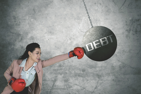 Picture of Caucasian businesswoman wearing boxing gloves while punching debt word on the pendulum 版權商用圖片