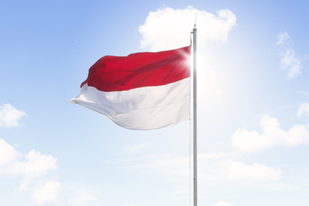 Image of Indonesia flag waving on a flagpole under blue sky Stock Photo