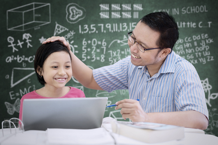 Portrait of Asian cute schoolgirl being praised by her teacher while sitting in the classroom