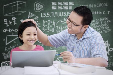 Portrait d'écolière mignonne asiatique félicité par son professeur alors qu'il était assis dans la salle de classe Banque d'images
