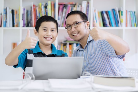 Image of young teacher showing thumbs up with his student while sitting in the classroom