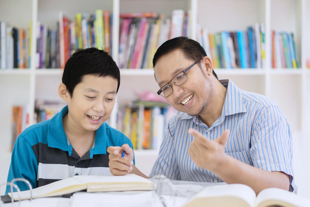 Picture of male teacher guides his student to count while sitting in the library Foto de archivo