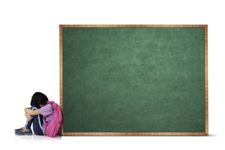 Picture of sad schoolgirl sitting with blank chalkboard, isolated on white background